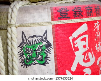NAGOYA, JAPAN - MARCH 28, 2018: Close-up detail of Kazaridaru, Sake barrel Shinto offerings, with painted green Oni ogre and red calligraphy lettering. Atsuta Shrine. Travel and religion.