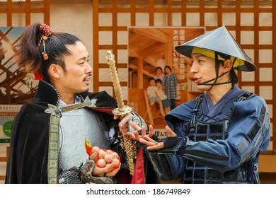 NAGOYA, JAPAN - NOVEMBER 21: Japanese Fair in Nagoya, Japan on November 21, 2013. Japanese vendor dresses old style warrior costume to promote his product at Nagoya Castle Fair