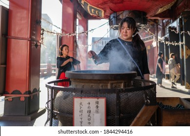 Nagoya, Japan - September 16 2019: A woman at the Osu Kannon temple lighting an incencse stick.