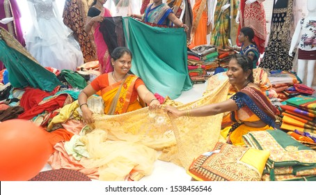NAGPUR, MAHARASHTRA, INDIA 17 SEPTEMBER 2019 : Cloth seller showing Saree to the customers in a shopping mall during diwali festival and family enjoying to Purchasing latest traditional Indian clothes