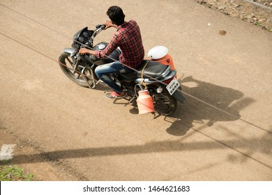 NAGPUR, MAHARASHTRA, INDIA 23 JUNE 2019 : Unidentified Indian Milkman transporting milk on two wheeler motor cycle for delivery