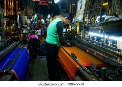 NAGPUR, MAHARASHTRA, INDIA 4 DECEMBER 2016 : Unidentified Indian man weaving traditional sari on loom, Nagpur is famous for hand woven traditional sarees.