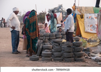 NAGPUR, MAHARASHTRA, INDIA, 7 AUGUST 2016 : Unidentified Indian stone cutter man selling stone pots in front of his hut.
