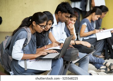 NAGPUR, MAHARASHTRA, INDIA, 9 APRIL 2016 : unidentified young students Surfing the net outdoors and working on laptop and smiling while sitting together on the outdoors staircase at campus.