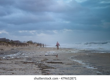 NAGS HEAD, NORTH CAROLINA - SEPTEMBER 4, 2016:  An unknown local searching through debris left on the beach from the aftermath of Hurricane Hermine's high winds and waves.