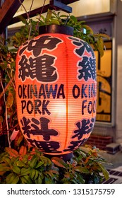 Naha, Okinawa / Japan - February 26th 2018: Colorful neon lantern and restaurant storefront advertising popular local delicacy of Okinawa pork
