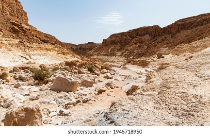 the Nahal Nekarot stream exits the south rim of the Makhtesh Ramon crater in Israel through the Nekarot Gap with a pale blue sky in the background