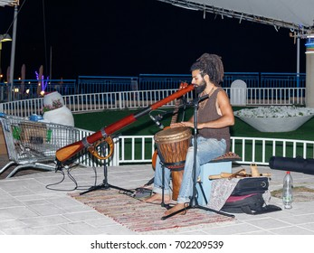 Nahariya, Israel, August 14, 2017 : A young guy plays a darbuka and a big pipe in the evening on the waterfront in the city of Nahariya, in Israel