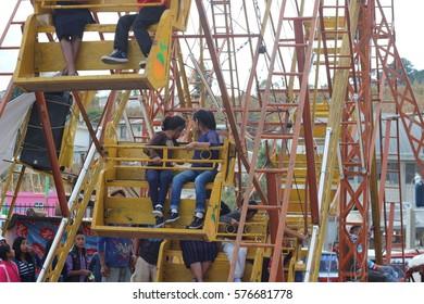 NAHUALA, GUATEMALA - CIRCA NOVEMBER 2016: Local Mayan children having fun on a Big Ferris Wheel at the local feria; the annual festival in Nahuala (highlands).