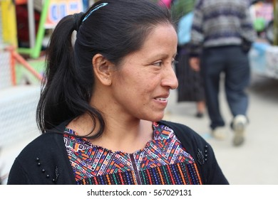 NAHUALA, GUATEMALA - NOVEMBER 2016: Portrait of Pascuala, a young Mayan woman having fun in her traditional handwoven traje (costume) at the feria, the annual local festival.