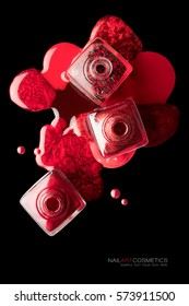 Nail art and beauty concept with trendy metallic red lacquer or nail polish spilled artistically around three square open bottles over a black background, top view  with copy space