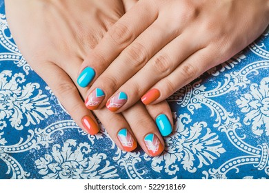 Nail art with bright orange and light blue chevron on pattern paper background
