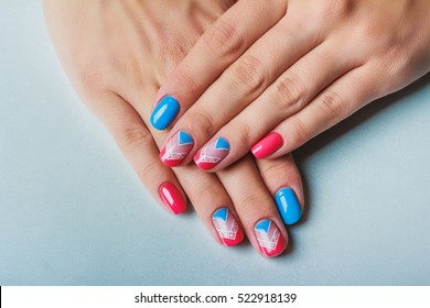 Nail art with bright pink and blue chevron pattern on light background