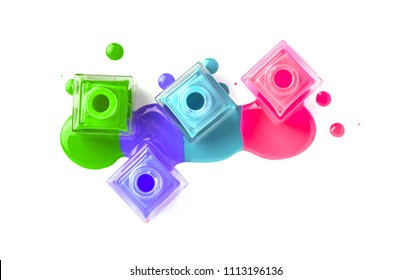 Nail art concept. Fine art cosmetics and beauty image of a group of three colorful nail polish bottles on spilled paint isolated on white. Top view, flat lay