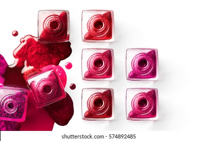 Nail art concept. Fine art cosmetics and beauty image of a group of eight square nail polish bottles on spilled metallic pink and red paint with copy space for text.