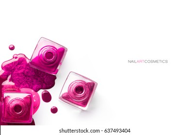 Nail art concept. Fine art cosmetics and beauty image with different shades of metallic pink nail polish artistically spilled around three open bottles. Top view isolated on white with copy space