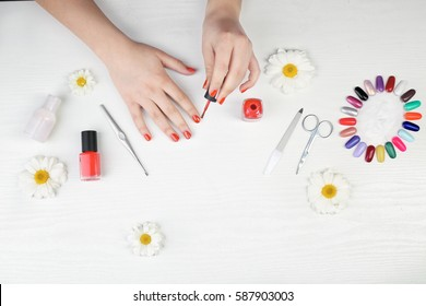 Nail art concept. Woman making manicure on white table