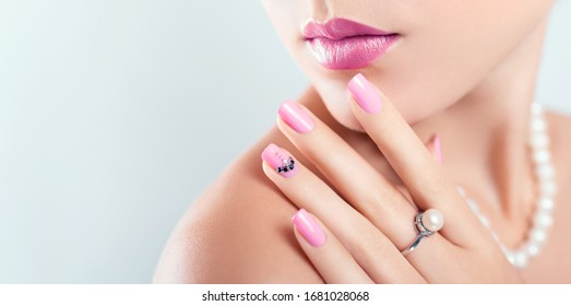 Nail art and design. Beautiful woman wearing make-up and pearl jewellery showing pink manicure with gems. Beauty fashion model. Skin care. Banner