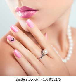 Nail art and design. Beautiful woman wearing make-up and pearl jewellery showing pink manicure with gems.