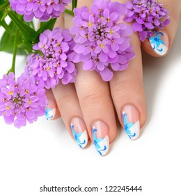 Nail art. Female nails with figure of petal blue color closeup and flower