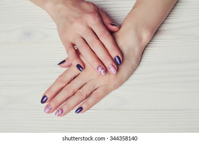 Nail art with purple and pink colors on wooden background