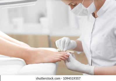 Nail artist in beauty salon making french pedicure for clients feet. Professional in mask on face polish nails by tool. Concept of nails, feet health and podiatrist proffeshion.