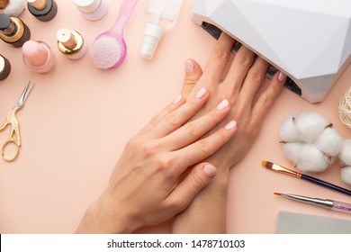 Nail care. beautiful women hands making nails painted with pink gentle nail polish on a pink background. Women's hands near a set of professional manicure tools. Beauty care