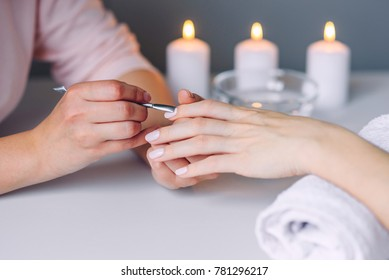 Nail care. Closeup of beautiful woman hands getting manicure in spa salon. Female manicurist cleaning cuticle with professional manicure pusher tool. Cosmetic procedure.