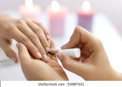 Nail Care And Manicure. Closeup Of Beautiful Female Hands Applying Transparent Nail Polish On Healthy Natural Woman's Nails In Beauty Salon. Manicurist Hand Painting Client's Nails. High Resolution
