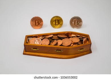"""Nail in the Coffin"". Bitcoins and the coffin full of 1p and 2p UK coins.Isolated on gray."