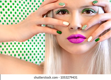 Nail design and makeup with green dots on model on background with dots.Fashion girl.Nail art.
