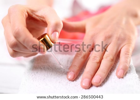 Nail painting. Woman paints the nails cuticle oil and nail