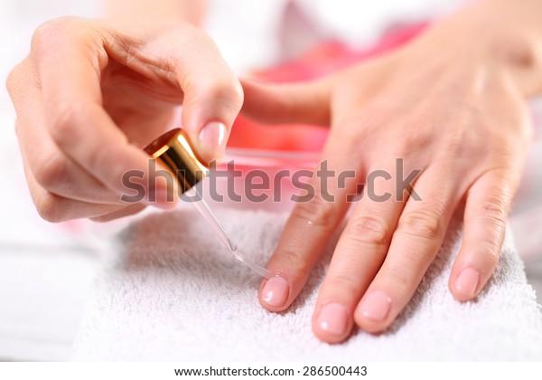 Nail painting. Woman paints the nails cuticle oil and nail