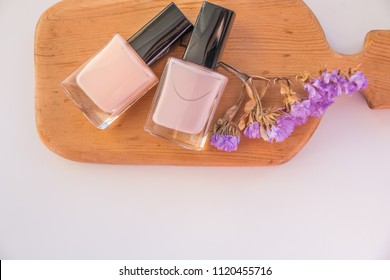 Nail Polish. Art Manicure. Modern nude pastel colors style. pastel pink bottles. Stylish nude Colors isolated on wooden board, white background. Classic wedding bride nails design