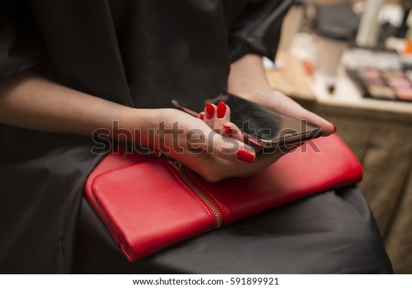 Nail Polish. Art Manicure. Modern red style. Beauty hands holding red bag clutch with black cell smart phone. Stylish woman by make up artist