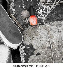 Nail polish bottle on ground next to abandoned shoe