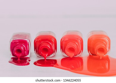 nail polish bottles in different shades of red to orange and purple spilling color on wooden surface, concept of cosmetics industry and manicure