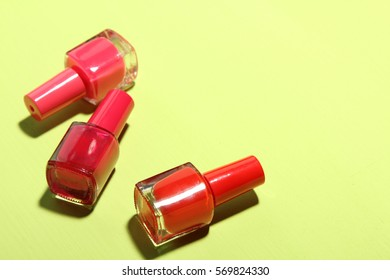 Nail polish red, pink colors on a yellow background.