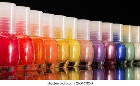 Nail polish in a row on black background
