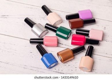 Nail polish with a variety of colors arranged on a solid background.