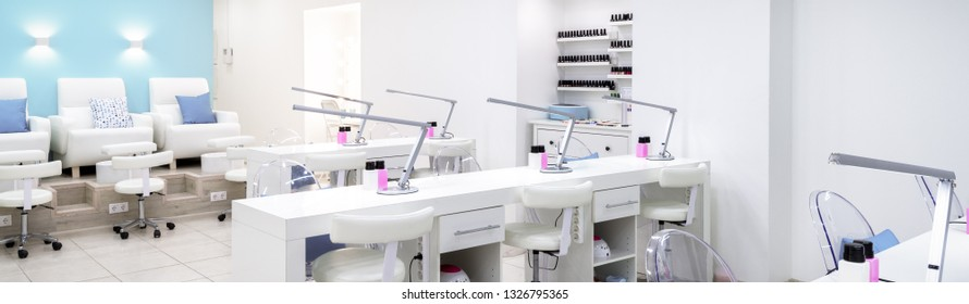 Nail salon bright interior. Panoramic view of a modern manicure salon. Horizontal banner with a spa room. Inside a beauty studio with white design.