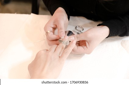 In the nail shop, the woman in the nail shop is getting a manicure at the nail shop hairdresser