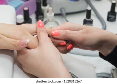 A nail specialist is rubbing oil into the client's hand. It turned out the ulug in the salon of the nail service