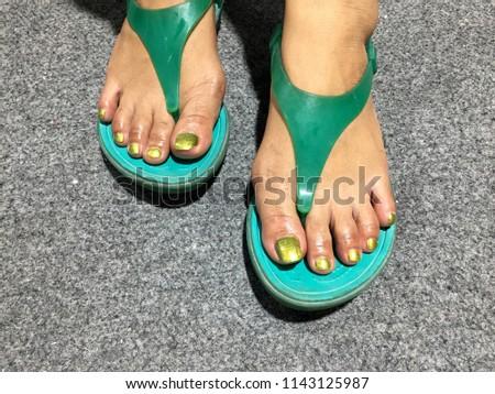 5ca2b8010f4d Nails art. Female feet wearing dark green sandals in light green pedicure  nail polish. Pedicure with green nail Polish. Nail design on grey carpet ...