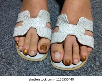 d58770ad94c6 Female feet in white sandals. Pedicure with white pearl and gold glitter