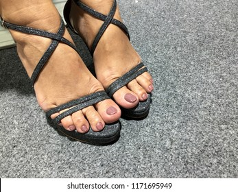 Nails art. One pair of black sandals high heels with purple nail feet. Woman feet in high heels summer sandals shoes.Grey carpet background.