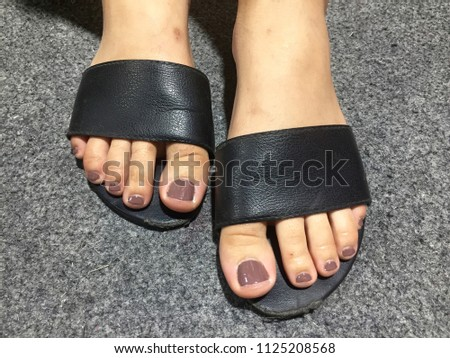 10d55b69af0c Nails art. Pedicure with purple colors of nail polish on a woman s feet in  black sandals. On grey carpet background. Winter Style. - Image