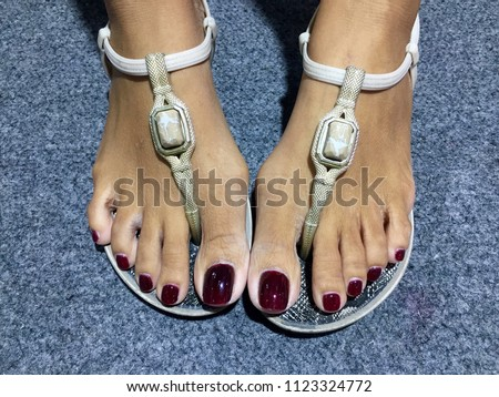 12c48732670e Pedicure with red burgundy colors of paint on a woman s feet in white  sandals. Female Feet Wearing White Sandals on grey carpet background. -  Image