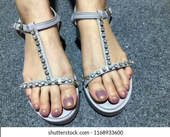 Nails art. Sexy feminine feet with gray sandals.Female foot in fashion sandals with diamonds. Woman feet in high heels summer sandals shoes with purple manicure nail polish. On grey carpet background.