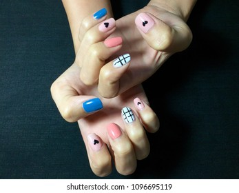 Nails art. Woman hands with painted fingernails, black hearts and lines. Female hands with pastel pink, hot pink, white and blue nail polish. Black background.Summer Spring Styles.